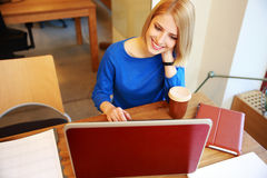 Woman using laptop in office Stock Images