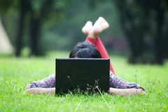 Woman using laptop outdoor. Unrecognized woman using laptop in the park lying on the green grass Stock Photos