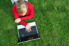 Woman using laptop outdoors. Young woman working on laptop outdoors Royalty Free Stock Image