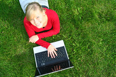 Woman using laptop outdoors. Young woman working on laptop outdoors Stock Photography