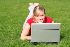 Woman using laptop outdoors. Young woman working on laptop outdoors Royalty Free Stock Photo