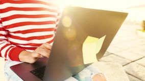 Woman using laptop outdoors against the setting sun stock footage