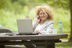 Woman using laptop in park Royalty Free Stock Image