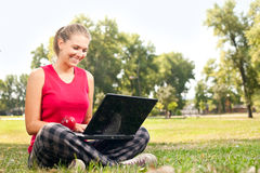 Woman using laptop in park Stock Image