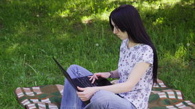 Woman using laptop in park. Adult woman sitting on grass and using laptop stock footage