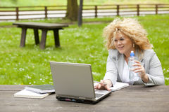 Woman using laptop in park and drink water Stock Images