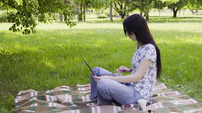 Woman using laptop in park. A female student sitting on lawn and using laptop stock video