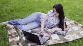 Woman using laptop in park. Woman freelancer lying on lawn and using laptop stock footage