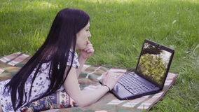 Woman using laptop in park. Serious woman lying on grass and using laptop stock video footage
