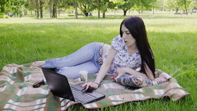 Woman using laptop in park. Woman student lying on grass and using laptop stock video footage