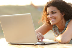 Woman using a laptop in a park at sunset Royalty Free Stock Photography