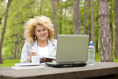 Woman using laptop in park on wooden table Stock Photography