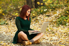 Woman using the laptop in the park Stock Photography