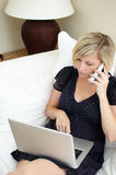 Woman using laptop and phone. High angle view of woman sat on sofa holding telephone and laptop computer royalty free stock images
