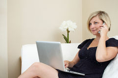 Woman using laptop and phone. Young woman relaxing in comfortable seat holding telephone and laptop computer Royalty Free Stock Photo