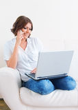 Woman using laptop and a phone on the sofa Stock Photos