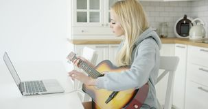 Woman using laptop while playing guitar stock video footage