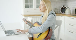 Woman using laptop while playing guitar Stock Photo