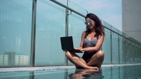 Woman using laptop in the pool on a sunny day stock video footage