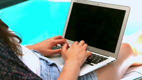Woman using laptop poolside stock video footage