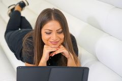 Woman using a laptop while relaxing on the couch Stock Photos