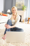 Woman Using Laptop Relaxing Sitting On Rug At Home Stock Photo