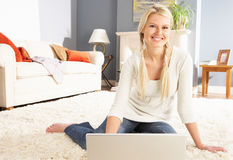 Woman Using Laptop Relaxing Sitting On Rug At Home Royalty Free Stock Image