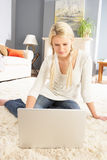 Woman Using Laptop Relaxing Sitting On Rug At Home Stock Photography