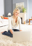 Woman Using Laptop Relaxing Sitting On Rug At Home Stock Images