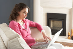 Woman Using Laptop Relaxing Sitting On Sofa Stock Photography