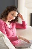 Woman Using Laptop Relaxing Sitting On Sofa Royalty Free Stock Image
