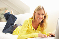 Woman Using Laptop Relaxing Sitting On Sofa Royalty Free Stock Image