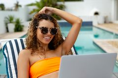 Woman using laptop while relaxing on a sun lounger in the backyard at home. Front view of happy mixed-race woman using laptop while relaxing on a sun lounger in royalty free stock photo