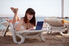 Woman using  laptop at resort beach Stock Image