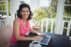 Woman using laptop in restaurant Stock Images