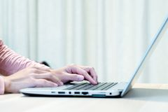Woman using laptop, searching, checking, browsing information at home Royalty Free Stock Photography