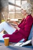 Senior woman using laptop sitting stock photos