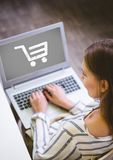 Woman using Laptop with Shopping trolley icon Stock Image