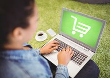 Woman using laptop with Shopping trolley icon Stock Photography