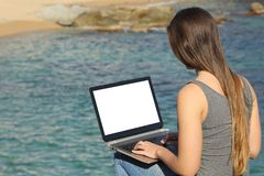 Woman using laptop showing blank screen on the beach. Woman using laptop showing blank screen on a beautiful beach on summer vacation stock photography