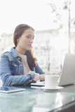 Woman using laptop at sidewalk cafe Royalty Free Stock Images