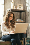 Woman using laptop while sitting in apartment Royalty Free Stock Photo