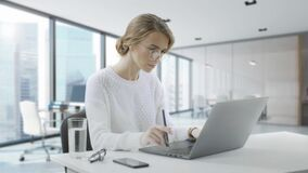 Woman is using laptop while sitting at her desk. Young european businesswoman is sitting in the office and working on