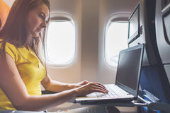 Woman using laptop while is sitting in plane near window. Woman using laptop while is sitting in plane near window Royalty Free Stock Photos