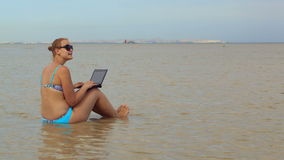 Woman using laptop sitting in the sea stock footage