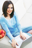 Woman using laptop, sitting on sofa. Royalty Free Stock Images