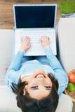 Woman using laptop, sitting on sofa. Royalty Free Stock Image