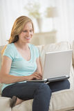 Woman Using Laptop While Sitting On Sofa Stock Images