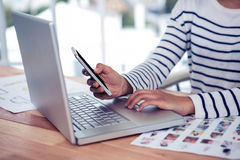 Woman using laptop and smartphone Royalty Free Stock Image