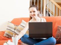 Woman using laptop on sofa Royalty Free Stock Photos
